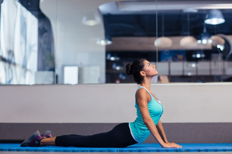 Portrait of a sports woman doing yoga exercises in gym